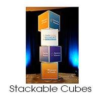 8 foot x 2 foot custom stackable cubes. Silver frames with printed artwork on each side.